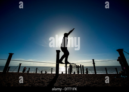A tightrope walker practices in the sunshine in front of the west pier in Brighton, Sussex, UK - Stock Photo