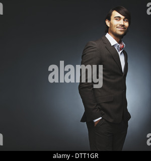 Attractive young man wearing suit standing with his hands in pocket looking over shoulder. Handsome male fashion - Stock Photo