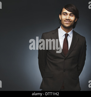 Handsome young man looking away smiling on black background. Male model in business suit looking at copyspace. - Stock Photo
