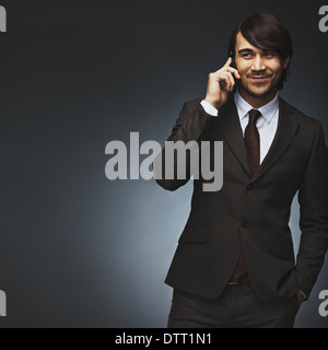 Asian man talking on mobile phone. Handsome young mixed race man on black background. Professional young businessman - Stock Photo
