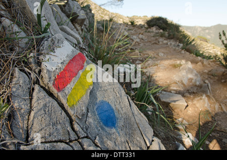 Hiking trail with marked signs painted on rock in Mijas, Spain. - Stock Photo
