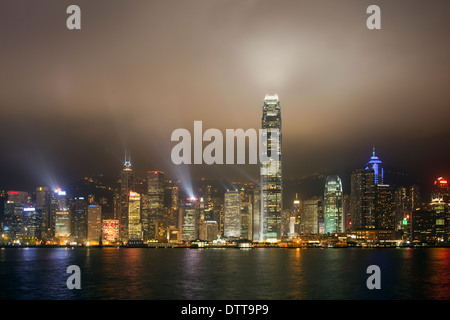 Hong Long waterfront at night with lasers projecting light beams into a misty grey-brown winter's sky at the nightly - Stock Photo