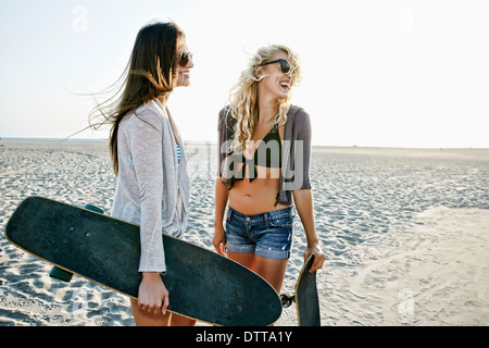 Women with skateboards standing on beach - Stock Photo