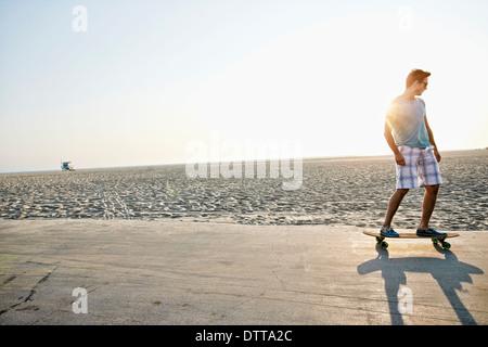 Caucasian man skating on beach