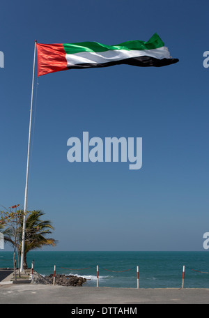 A UAE flag blowing in the window with the Arabian Gulf in the background.This was taken in Ras Al Khaimah in the - Stock Photo