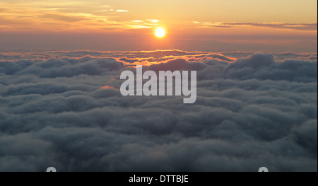 Sun rising over low lying clouds seen from mountain top, Drakensberg, Kwazulu-Natal, South Africa - Stock Photo