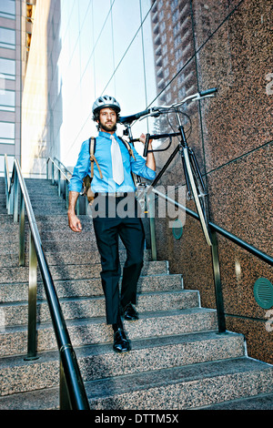 Caucasian businessman carrying bicycle down urban stairs - Stock Photo