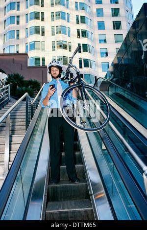 Caucasian businessman carrying bicycle on escalator - Stock Photo