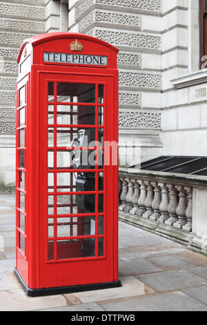 British red phone box on a London street - Stock Photo