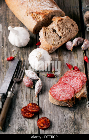 Sandwich and set of salami sausages with fresh bread, garlic and chili peppers served, vintage tableware on old - Stock Photo