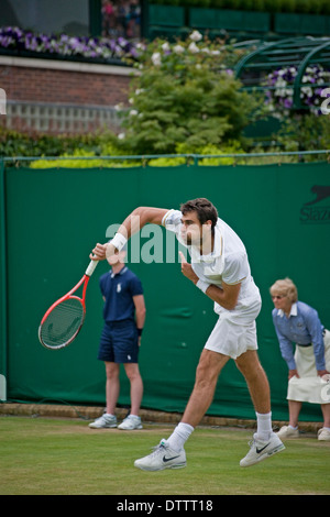 male tennis player stretching to serve shot at Wimbledon tennis championship - Stock Photo