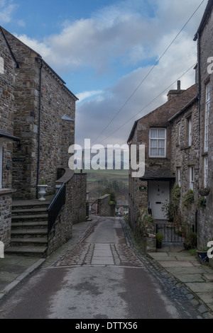 Stone built houses, on either side of a narrow road leading downhill - Stock Photo