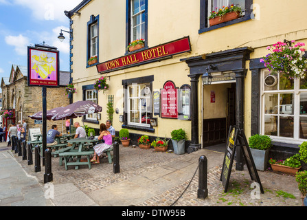 People sitting outside the Town Hall Hotel pub in the historic Market Place, Richmond, North Yorkshire, England, - Stock Photo