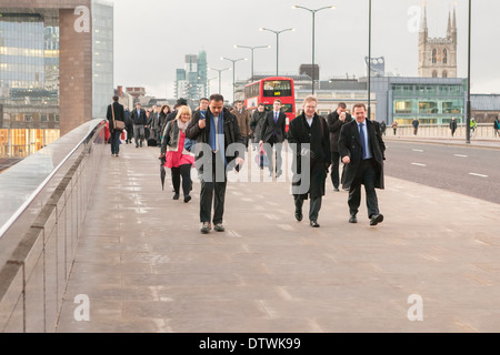 Commuters on London Bridge, London, UK, early morning - Stock Photo