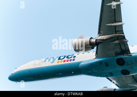 Underneath view of a Flybe Embraer short haul aeroplane flying directly overhead - Stock Photo