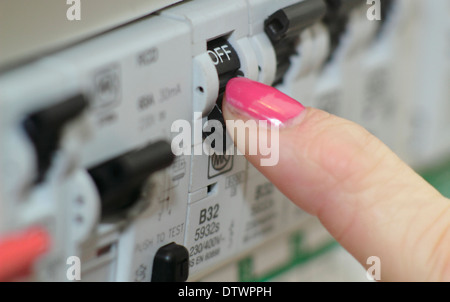 Woman switches trip/residual current device (RCD) / consumer unit in a domestic setting/home - Stock Photo