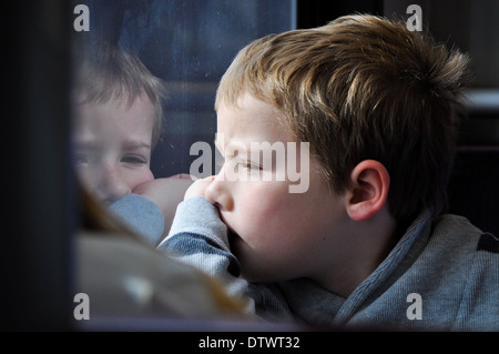 young boy lost in thought looking out of window - Stock Photo