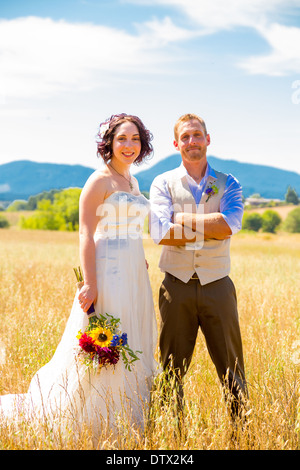 Bride and groom walking together on their wedding day through a field in Oregon. - Stock Photo