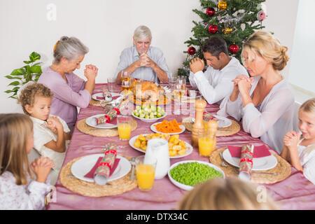 Family saying grace before christmas dinner - Stock Photo