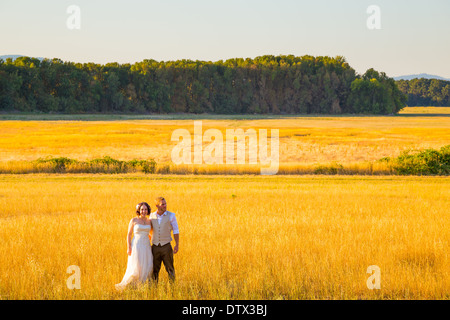 Wedding couple shares a romantic moment in a field or meadow at sunset on their wedding day. - Stock Photo