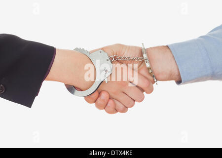 Business people in handcuffs shaking hands - Stock Photo