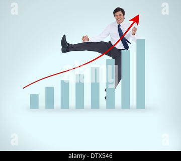 Smiling man in suit jumping over the graph - Stock Photo