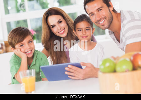 Happy family using a tablet pc - Stock Photo