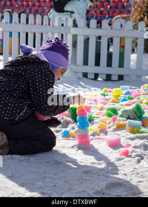 Coloured Ice Sculpture. A child uses coloured blocks of ice to build a simple ice sculpture at Ottawa's Winterlude - Stock Photo