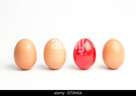 Four eggs in a row with one red one - Stock Photo