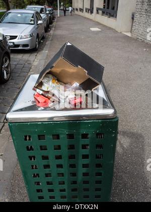 Public rubbish bin overflowing. - Stock Photo
