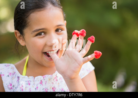 Mixed race girl eating raspberries on fingers outdoors - Stock Photo