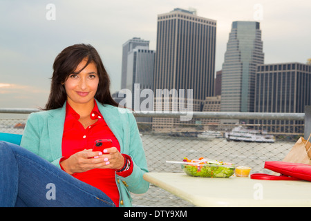 Mixed race woman eating lunch by urban river, New York, New York, United States - Stock Photo