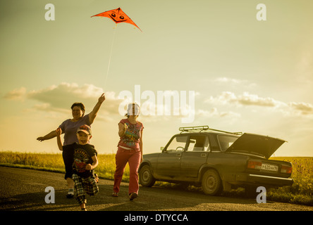 Caucasian family flying kite on rural road - Stock Photo