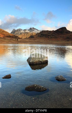 Rocks in the foreground, and the Langdale Pikes are reflected in the waters of Blea Tarn, Lake District National Park, England