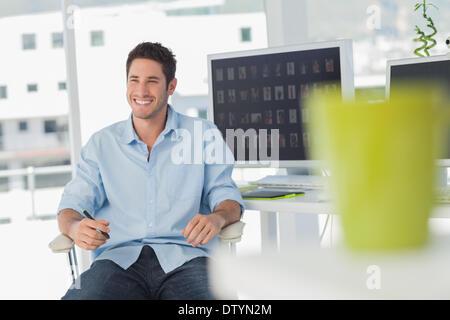 Cheerful photo editor in his swivel chair - Stock Photo