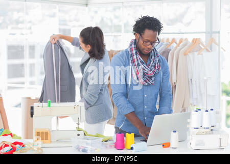 Fashion designer working on laptop - Stock Photo
