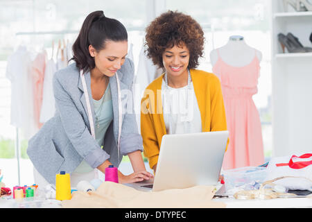 Fashion designers working on a laptop - Stock Photo
