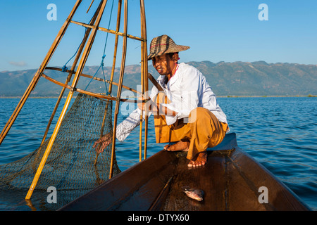 Fishermen with a traditional basket, caught fish in the canoe, Inle Lake, Shan State, Myanmar - Stock Photo