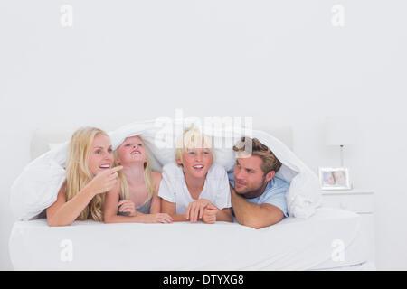 Happy family under the duvet - Stock Photo