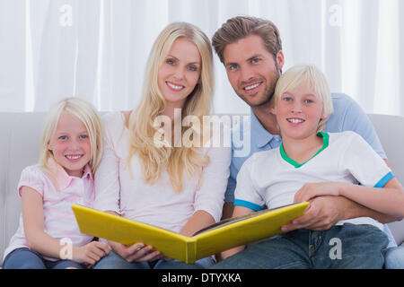 Portrait of a family holding a story book - Stock Photo