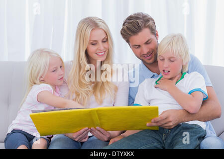 Happy family reading a story together - Stock Photo