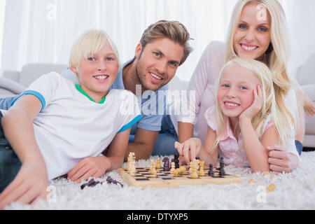 Smiling family playing chess together - Stock Photo
