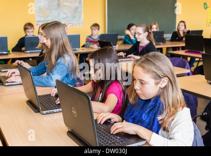 Junior high school students (about 12 years old) work with their laptops in their classroom. - Stock Photo