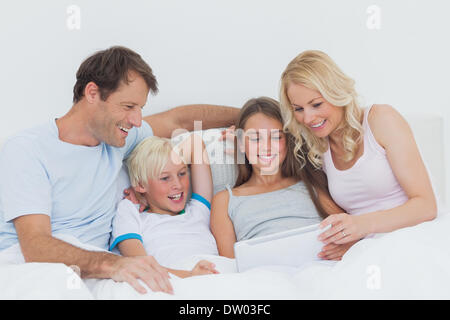 Cheerful family using digital tablet - Stock Photo