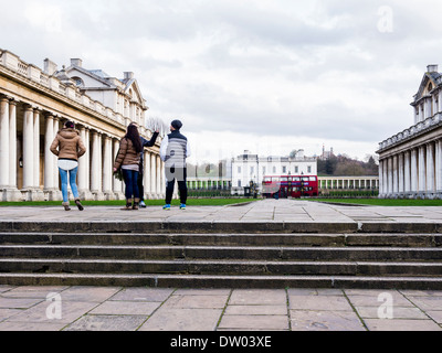 Young tourists look at Old Royal Naval College buildings and Queen's House Greenwich, London, UK - Stock Photo