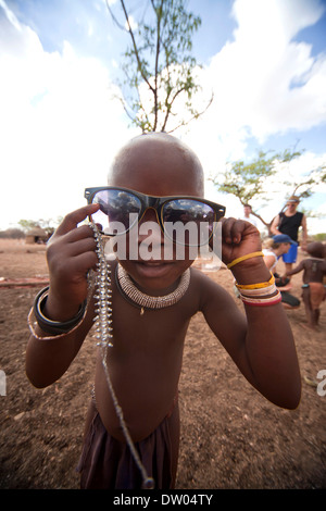 Himba child wearing traditional clothes and sunglasses in a typical village near Kamanjab, Namibia - Stock Photo
