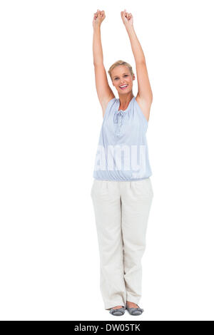 Excited woman standing with arms raised - Stock Photo
