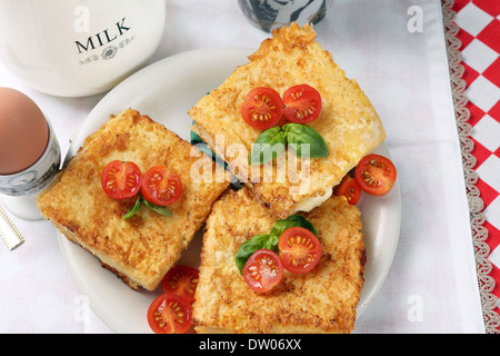 Toast with cheese and tomatoes, served with fried egg and a cup of milk - Stock Photo
