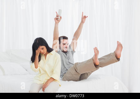 Woman annoyed at her partner watching tv - Stock Photo