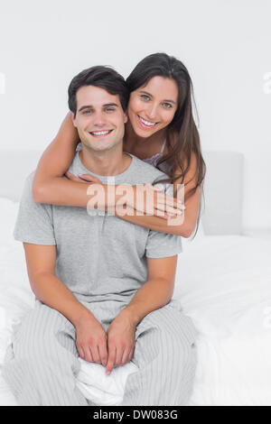 Woman embracing her partner sat in bed - Stock Photo